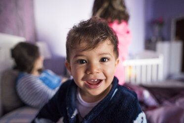 Portrait of laughing toddler in bedroom - JASF01812