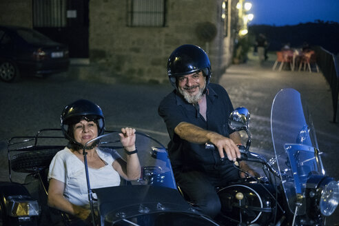 Spain, Banos de la Encina, portrait of mature couple on motorcycle with a sidecar at night - JASF01818