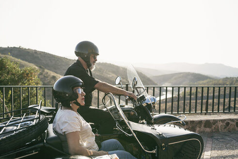 Spain, Jaen, mature couple on motorcycle with a sidecar on a bridge - JASF01821