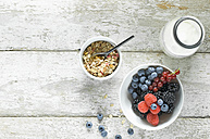 Bowl of granola, milk bottle and bowl of berries on wood - ASF06105