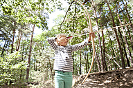 Girl shooting with bow and arrow in the forest - MFRF00978