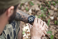 Close-up of man in forest checking the time - MFRF00996