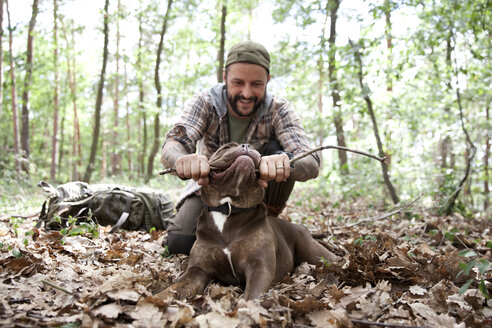 Man playing with dog in forest - MFRF01005