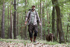 Man with bow and arrow walking with dog in forest - MFRF01011