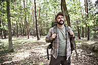 Serious man with backpack on a hiking trip in forest - MFRF01017