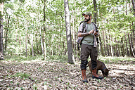 Man with dog on a hiking trip in forest using cell phone - MFRF01020