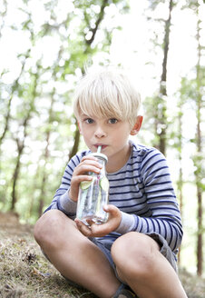 Boy drinking from glass of infused water in forest - MFRF01035