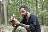 Man looking at carved wooden boat in the forest - MFRF01044