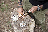 Man igniting a fire on tree stump in the forest - MFRF01047