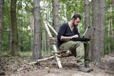 Man sitting on self-made wooden chair in forest using laptop - MFRF01050
