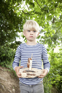 Boy holding carved wooden boat in forest - MFRF01056