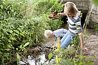 Boy and girl playing with carved wooden boat in brook - MFRF01059