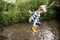 Excited girl jumping into brook - MFRF01062