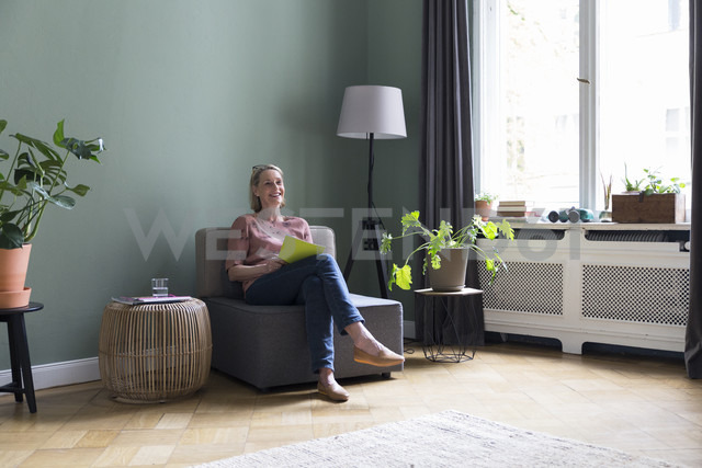 Smiling mature woman sitting at home - RBF05845