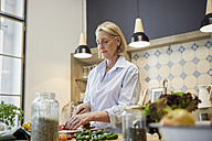 Mature woman chopping bell pepper in kitchen - RBF05878