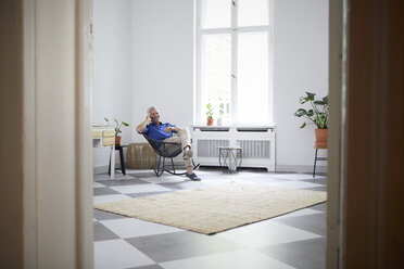 Smiling mature man on cell phone at home - RBF05896