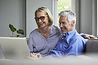 Happy mature couple sitting on couch at home sharing laptop - RBF05902
