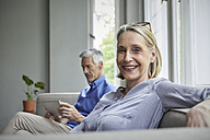 Portrait of smiling mature woman on couch with man in background using tablet - RBF05905