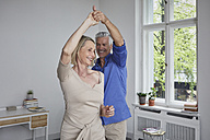 Happy mature couple dancing at home - RBF05911
