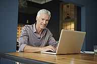 Portrait of mature man using laptop on table at home - RBF05923