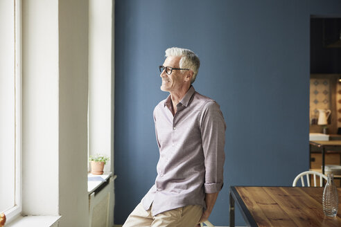 Confident mature man at home looking out of window - RBF05926