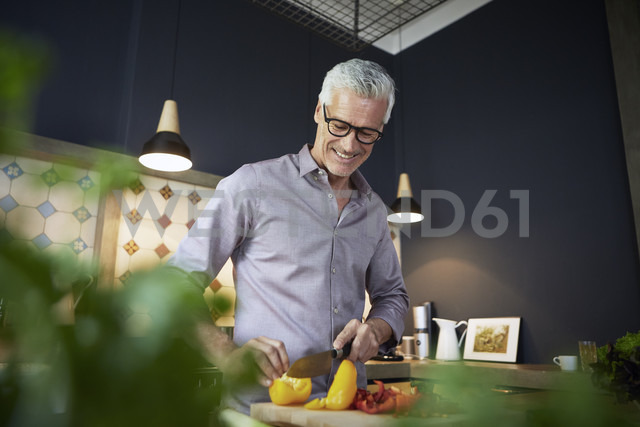 Smiling mature man chopping bell pepper in kitchen - RBF05929 - Rainer Berg/Westend61
