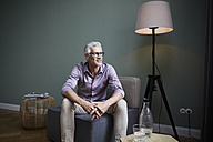 Mature man sitting on armchair at home - RBF05935
