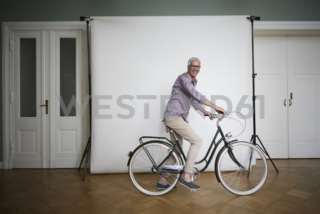 Portait of mature man posing on bicycle at projection screen - RBF05938