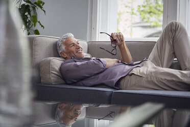 Smiling mature man lying on couch at home - RBF05941