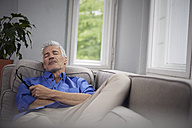 Portrait of mature man relaxing on couch at home - RBF05947
