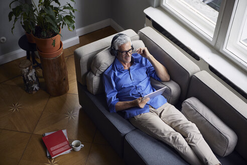 Smiling mature man with tablet and headphones relaxing on couch at home - RBF05950