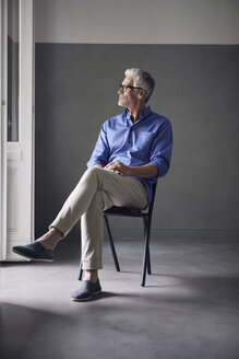Pensive mature man sitting on chair  at home looking at distance - RBF05953