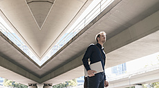 Businessman standing at underpass holding laptop, composite - KNSF02475