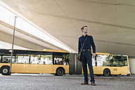 Businessman standing at underpass with bus in background - KNSF02481