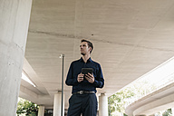 Businessman standing at underpass holding tablet - KNSF02484