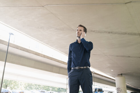 Businessman on cell phone at underpass - KNSF02487
