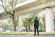 Businessman standing outdoors at a bridge - KNSF02499