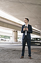 Businessman standing at underpass holding tablet - KNSF02502
