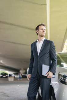 Businessman standing next to car holding laptop - KNSF02508