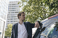 Businessman standing next to car with reflection of an office tower - KNSF02511