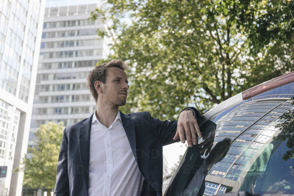 Businessman standing next to car with reflection of an office tower - KNSF02511 - Kniel Synnatzschke/Westend61