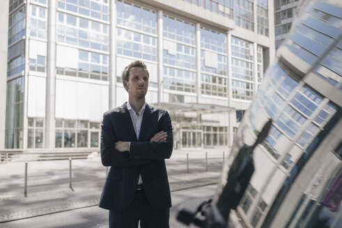 Businessman standing next to car with reflection of an office tower - KNSF02514