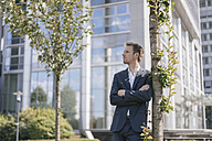 Businessman leaning against a tree in front of office building - KNSF02517