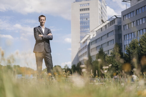 Businessman standing on field in front of office buildings - KNSF02520