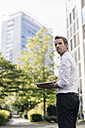 Businessman using laptop in front of office building - KNSF02535