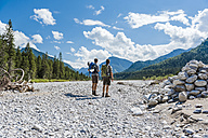 Germany, Bavaria, back view of two hikers standing in dry creek bed looking at view - DIGF02779