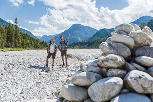 Germany, Bavaria, two hikers standing in dry creek bed looking at view - DIGF02782