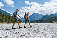 Germany, Bavaria, two hikers walking in dry creek bed - DIGF02785