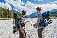 Germany, Bavaria, two hikers  standing in dry creek bed orientating with cell phone and map - DIGF02791