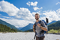 Germany, Bavaria, portrait of young hiker with backpack and hiking poles - DIGF02797